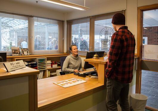 En student får hjelp av en medarbeider i infosenteret.