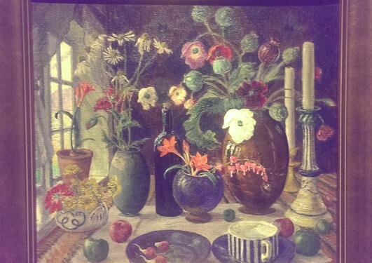 An Astrup painting of a table with flowers, a cup and a plate, fruits