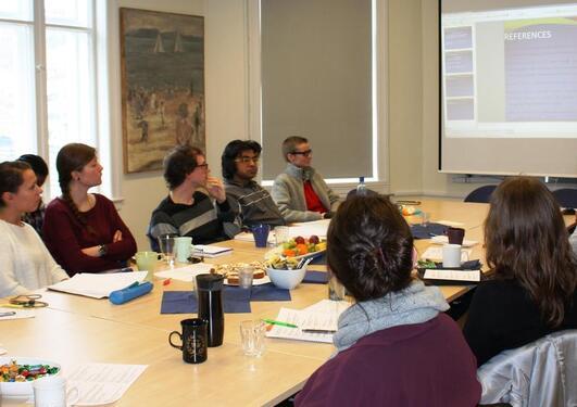 Flere personer rundt et møtebord, en person som presenterer