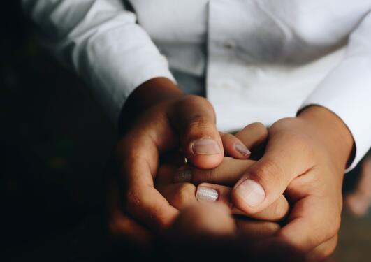 En person som holder en annen sin hånd