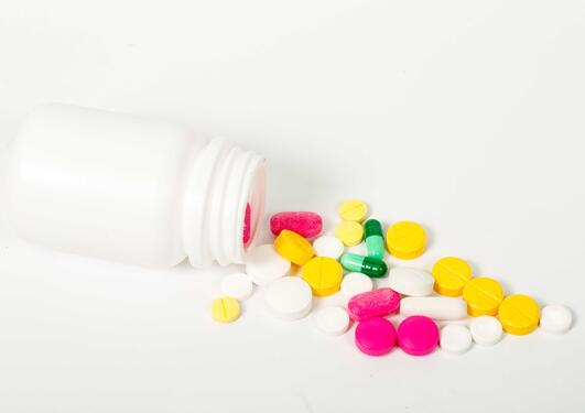 Bottle of medicines, showing the bottle tipped over with pills in various colours. Used to illustrate article about the Centre for Personalized Immunotherapy at University of Bergen.