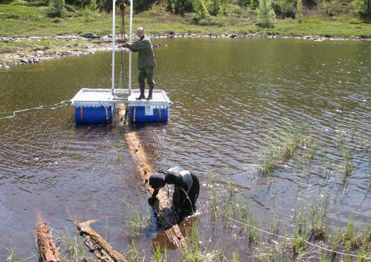 One man on a raft and another securing a fossil tree trunk to remove it from a lake
