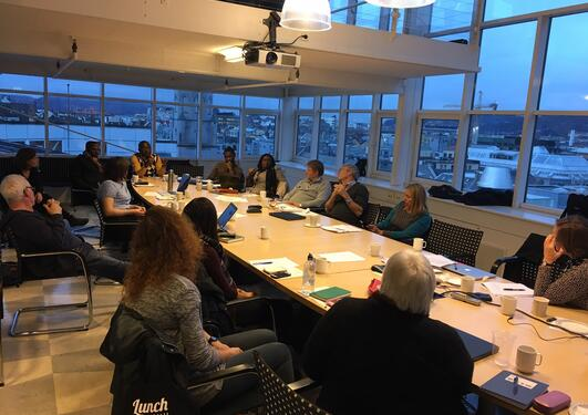 People attending a workshop, sitting around a conference table, talking