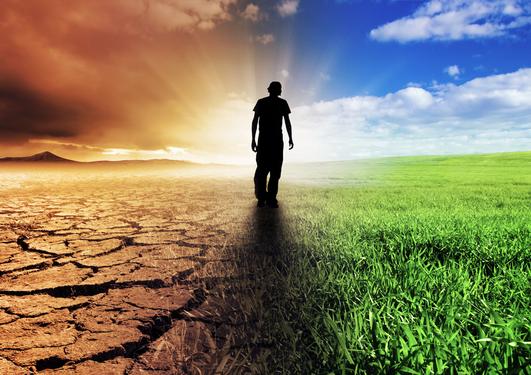Et menneske som går med dødt landskap på venstre side og grønt og frodig landskap på høyre side.