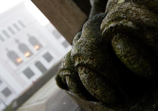 Foten til løva ved Christie-statuen, med museet i bakgrunnen.