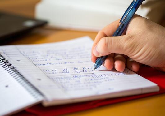 Person som skriver i en notatblokk