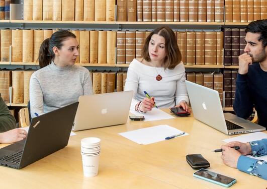 Fem studenter sitter rundt et bord med laptop.