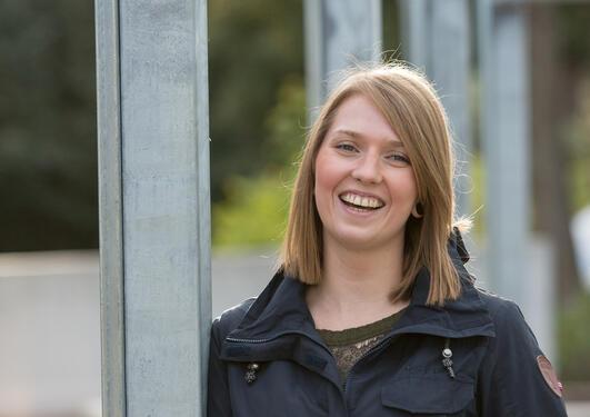 Ung kvinne smiler til kamera