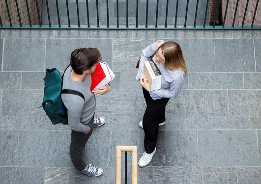 To studenter holder pensumbøker på Jussbygget
