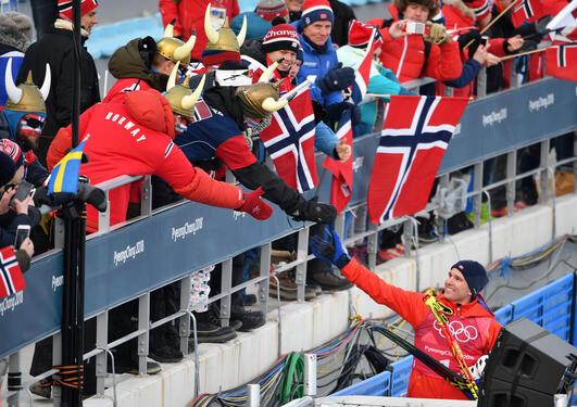 Publikum på tribunen og Didrik Tønseth etter stafett herrer, OL i Pyeongchang Sør-Korea