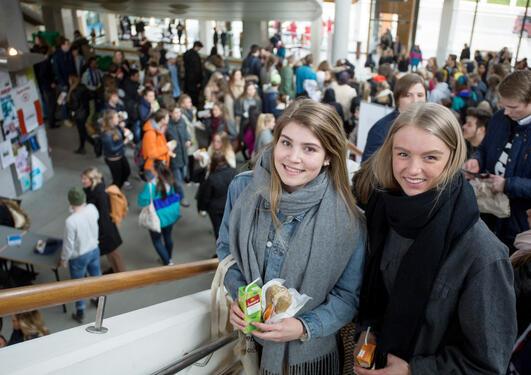 To jenter står i forgrunnen i trappen på Studentsenteret, bak ser du mange elever, en stor folkemengde