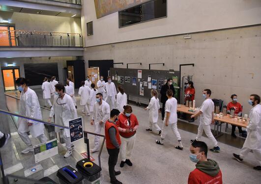 Studenter og personell samlet i Vrimleområdet i BB-bygget før eksamen. Studentene i hvite frakker med munngind, personell i røde trøyer