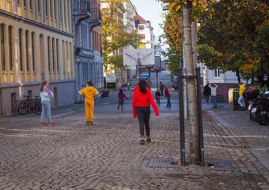 Bildet viser lekende barn i en gate.