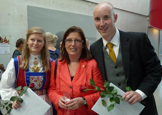 To uteksaminerte kandidater med rose og vitnemål i hånd. Mellom dem står profesor Jutta Dierkes.