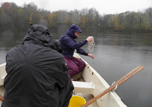 Two persons sampling with a plankton net from a boat on a rainy autumn day