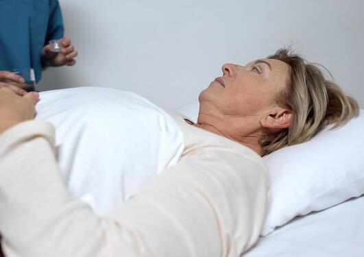Pasient mottar medisiner på sykehus