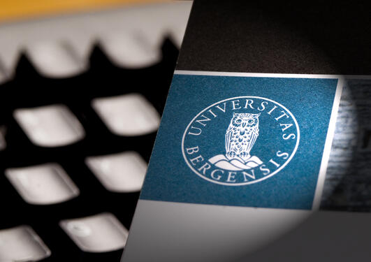 Keyboard and the UiB logo on paper