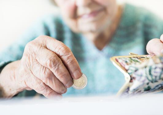 Gammel dame putter en mynt i lommeboken sin