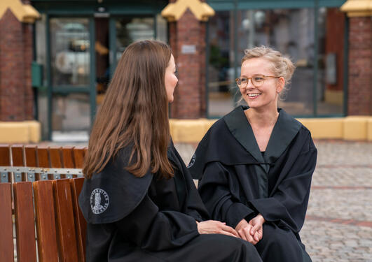 To kvinner i doktorkapper sitter og snakker på en benk utenfor Det juridiske fakultet