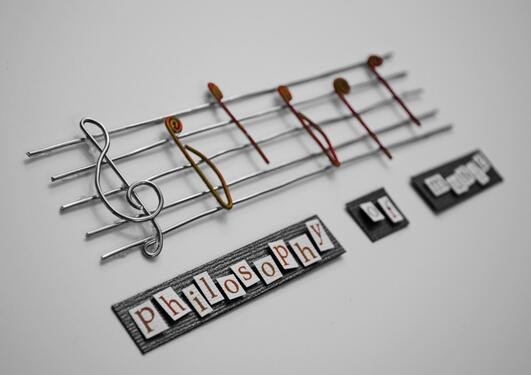 "Some musical notes with the text ""philosophy of music"" beneath"
