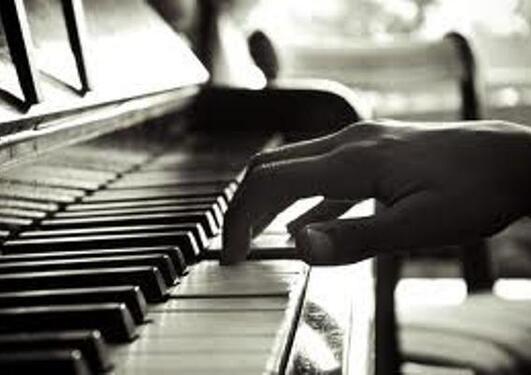 Sort hvitt bilde av tangenter og en hånd