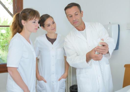 Nurses looking at apparatus