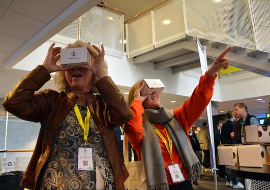 Unni Dahl og Sylvia Stokke prøver VR-briller på UiBs stand på Nordiske mediedagar
