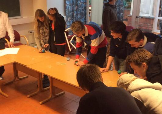 Elever forsøker å løse matematikkoppgaver stående rundt et bord hvor de bruker små globuser