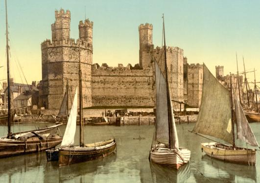 Fargefoto av plass i Wales i 1890-åra. Nokre båtar på vatn framfor ei borg frå mellomalderen.