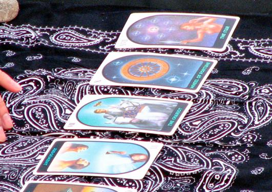 Spåing med tarot-kort. Hand med kort på svart duk.