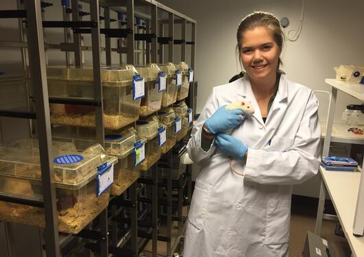 Stipendiat Andrea Rørvik Marti holder en rotte inne på laboratoriet