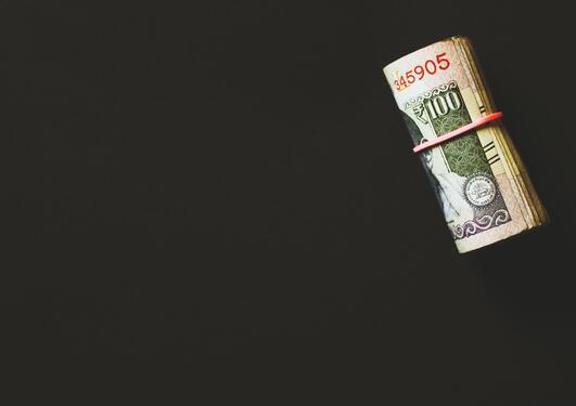 Penger i en rull på svart bakgrunn