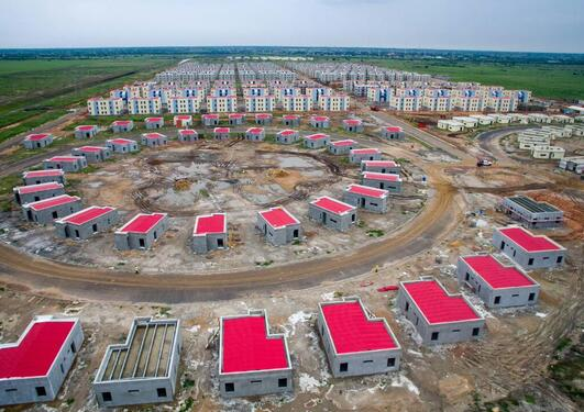 drone photo of an abandon buliding site, showing several houses built in a circle formation. Those that have a roof has a bright red roof.