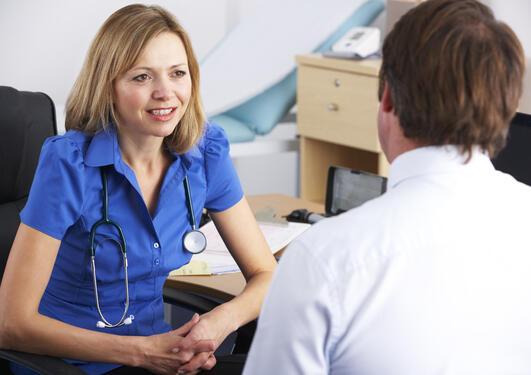 Bildet viser en lege som snakker med en pasient