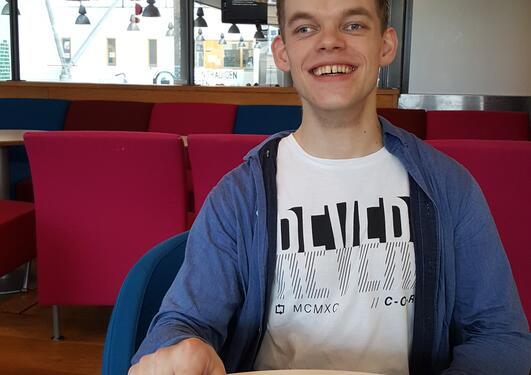 Mannlig student sitter ved kafébord med kaffekoppen foran seg.