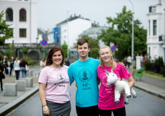 Three students with Mentor week t-shirts on, posing with a plush unicorn