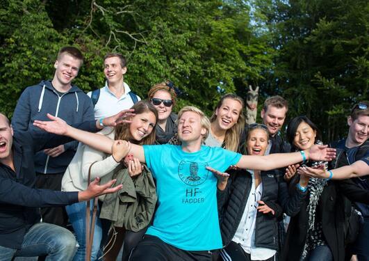 Glade nye studenter omkranser en fadder fra HF-fakultetet ved UiB