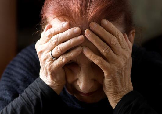 En eldre dame med ansiktet i hendene og et fortvilet uttrykk-