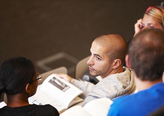 Ung mann ser til siden i forelesningssal