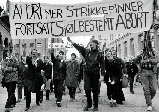 """Svart-kvitt bilete av demonstrasjon, der det fremste banneret viser teksten """"Aldri mer strikkepinner - fortsatt sjølbestemt abort"""""""