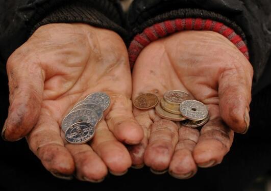 Bilde av et par skitne hender som holder noen mynter.
