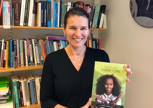 """Marit Skivenes med et eksemplar av boken """"Barnas barnevern"""""""