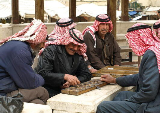En gruppe beduinmenn spiller brettspill på torget i Salt, Jordan.
