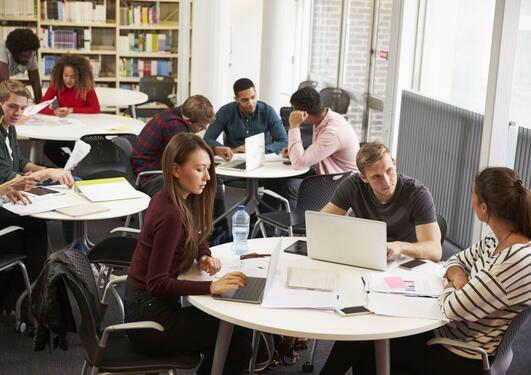 Studenter diskuterer på biblioteket