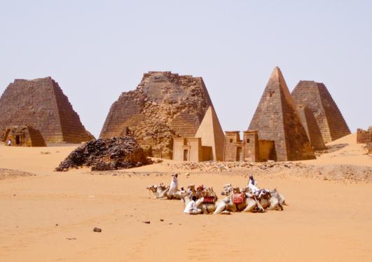 Kamelar og folk framfor ymse pyramidar i Sudan