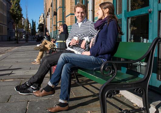 To studenter drikker kaffe og diskuterer i solen på en benk utenfor SV-fakultetet