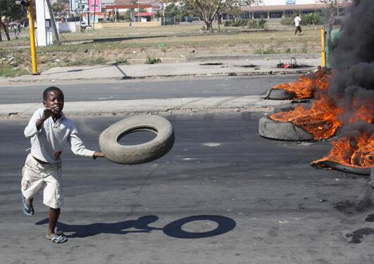 Gutt kaster et bildekk under gateopptøyer i Mosambik