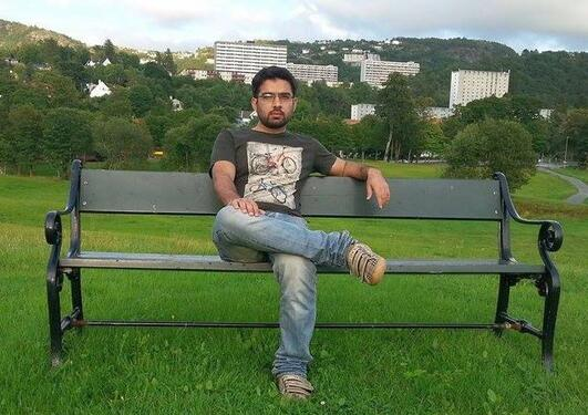Syed sitting on a bench in a park