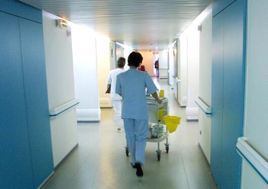 Helsearbeider går nedover en korridor og ruller på en tralle