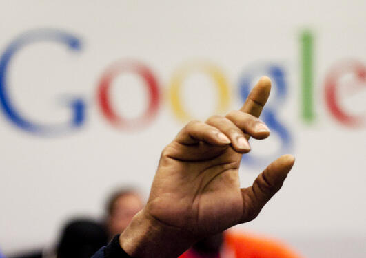 Hand with forefinger pointing upwards in front of the Google logo, used to illustrate article about legal challenges with privacy and search engines in the EU.